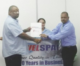 David Goberdhan, Station Manager of Travel Span and Sophia Fredericks Travel Consultant hand over the cheque to Rose Hall Town Youth and Sports Club's Hilbert Foster.