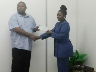 Dionne Johnson, Sales Supervisor of Mohammed's Enterprise, hands over the sponsorshgip cheque to Hilbert Foster of the Rose Hall Town Youth and Sports Club.