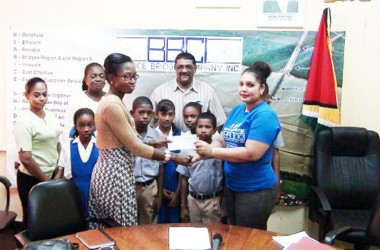 BBCI Administrative Assistant Bibi F Alli (right) presents a sponsorship cheque to a Region Six Regional Mashramani Committee member for the Spelling Bee competition while a number of children and officials look on