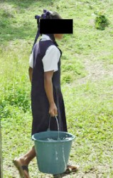 A Santa Rosa Primary student fetching a bucket of water