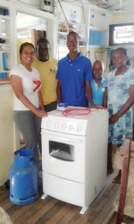 Vidya B. Sanichara - Digicel Communica-tions Manager (at left) donates the gas stove to the Dundas family