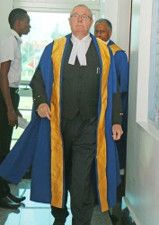 Justice David Hayton striding into the Guyana International Conference Centre, Liliendaal, East Coast Demerara yesterday morning for the inaugural sitting of the CCJ here. (Photo by Arian Browne)