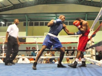 Best male boxer of the Goodwill Boxing Tournament, Dennis Thomas, (blue) on the attack against Jamaican, Michael Gardner in the bout of the tournament.