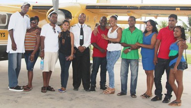 The five couples stand with pilot Learie Barclay (fifth from left) before the aerial tour of Georgetown on Sunday.