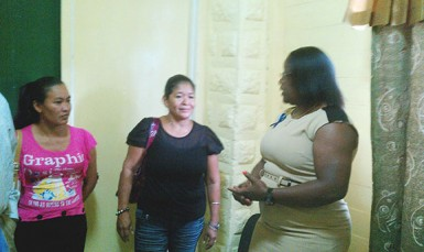 From left are Fatima Martin's sister Charmain Martin, her aunt Gloria Johnson talking to Simona Broomes yesterday.