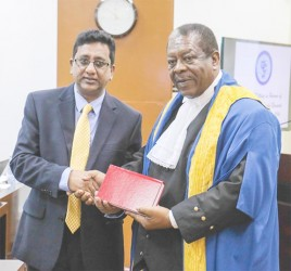 Attorney General Anil Nandall (left) yesterday handed over copies of Guyana Law Books and Law Reports to the Caribbean Court of Justice (CCJ), following a special sitting in honour of Justice Desiree Bernard. In this Arian Browne photo, Nandlall hands over one of the books to President of the CCJ, Sir Dennis Byron.
