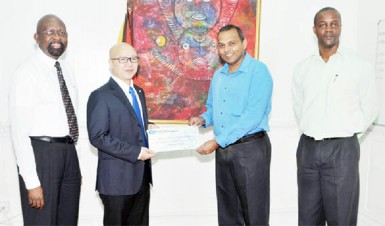 CHEC CJIA Project Manager Kevin Liu (second from left) hands over the cheque to Culture Minister Dr Frank Anthony. Also in photo from right are Permanent Secretary in the Ministry of Culture, Alfred King and Alex Graham of Tagman Inc. (CHEC photo)