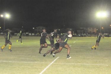UG's star forward, Ryan Dey (with ball) trying to elude a Caribs fullback. (Orlando Charles photo)
