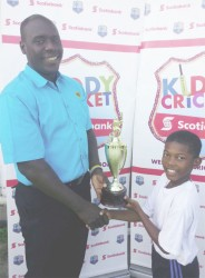 Coordinator Colin Stuart presents the winner's trophy for the South Georgetown Zone to Captain of the South Ruimveldt Primary School cricket team Oshazay Savory.