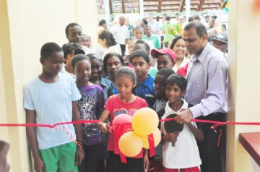 Minister of Sport, Dr. Frank Anthony watches on as a young sportswoman symbolically cuts the ribbon to open the National Resource Centre. (Orlando Charles photo)