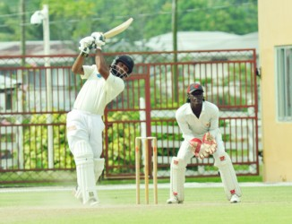 Assad Fudadin goes over extra cover during his unbeaten 117 while the national team's skipper Leon Johnson punches one off the back-foot in his 46
