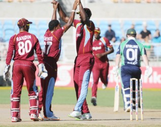 Krishmar Santokie and his teammates celebrate the fall of Paul Stirling's wicket. (WICB media photo)
