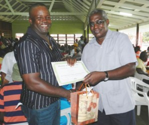 Irvin Stephens (left) receives his certificate from Minister Robeson Benn. (Ministry of Public Works photo)
