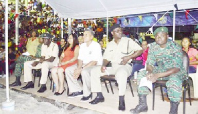 Minister of Amerindian Affairs Pauline Sukhai (fourth from right) and Region Seven Chairman Gordon Bradford (third from right) at the Republic Anniversary flag raising ceremony in the region. (GINA photo)