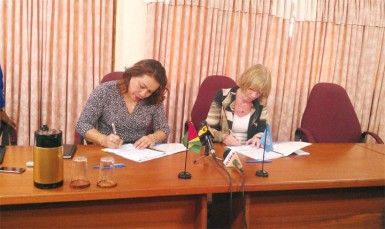 Foreign Affairs Minister Carolyn Rodrigues-Birkett (left) and UNICEF's Resident Representative Marianne Flach sign the Government of Guyana - UNICEF Annual Work Plan.