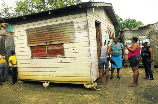 Relatives and friends gather at the small board house where Rosemarie Wilson and her commonlaw- husband Junior Pilliner were shot dead last week, leaving eight children orphaned.