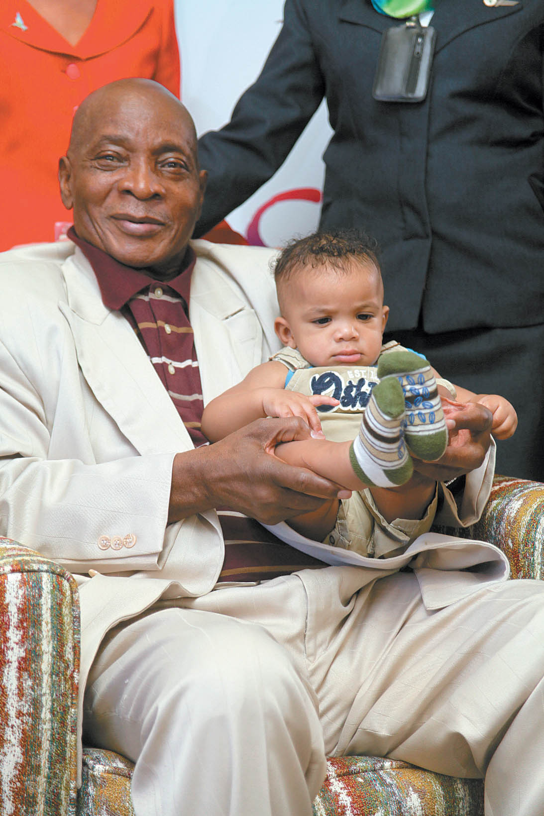 Calypso King of the world, Slinger Mighty Sparrow Francisco plays with his nine-month-old grandson, Kona Williams, in the VIP Lounge at the Piarco International Airport yesterday after he returned home from New York. Sparrow, now recovered from a stroke last year, is looking froward to the Carnival season.  (Trinidad Guardian photo)