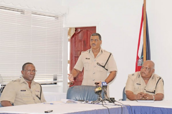 Assistant Commissioner David Ramnarine (centre) yesterday updating the media on the 71 recommendations made by the Discipline Forces Commission (DFC) for the reform and modernisation of the Guyana Police Force. In this Arian Browne photo Assistant Commissioner Balram Persaud (right) and another police officer look at the PowerPoint presentation being made by Ramnarine.