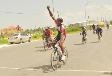Double winner Michael Anthony raises his hand in  triumph after winning the first stage of the 17th annual Dr Cheddi Jagan Memorial cycle road race in West Demerara yesterday. (Orlando Charles photo)