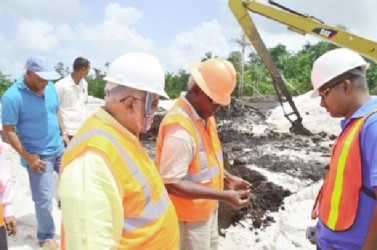 President Donald Ramotar (left) and Minister of Public Works, Robeson Benn (second from left) inspecting soil at the airport (GINA photo)