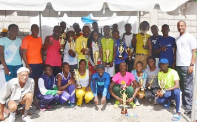 The winners pose for a group photo opportunity with president of the Athletic Association of Guyana Aubrey Hutson, right. (Orlando Charles photo)