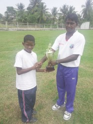 Captain, Shamal Taylor of Helena Primary receives the trophy from Latchman Yadram.