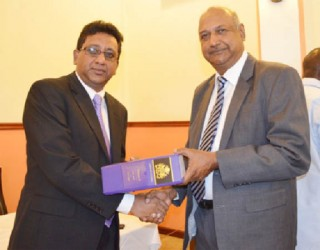 Minister of Legal Affairs and Attorney General Anil Nandlall (left), presenting a copy of the revised Laws of Guyana, to Chancellor of the Judiciary (ag), Carl Singh. (Government Information Agency photo)