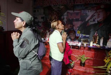 "A military woman and a local resident pray at the ""Saint Hugo Chavez"" altar at the 23 de Enero neighbourhood in Caracas March 5, 2014. REUTERS/Tomas Bravo"