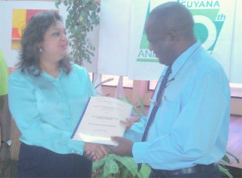 Education Minister Priya Manickchand presents one of the contracts to University of Guyana Vice-Chancellor Jacob Opadeyi.