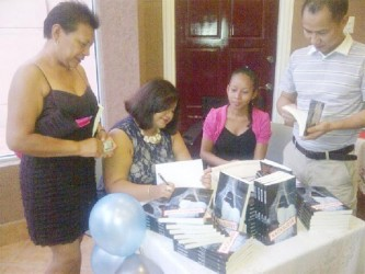Julia Kanhai signing copies her recent book launch.