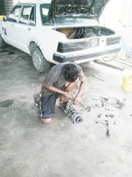 Kishan working on a car