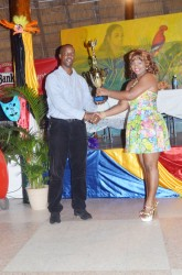 Designer of Digicel's costume, Olympia Small-Sonoram (right) receiving her prize from Permanent Secretary, Alfred King for Designer of the year
