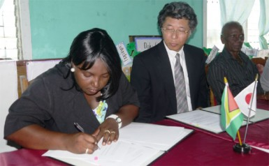 Jacqueline Cummings-Johnson and Ambassador, Yoshimasa Tezuka during the signing ceremony