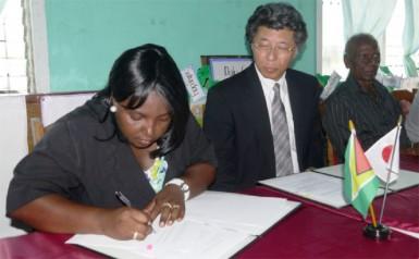 Jacqueline Cummings-Johnson and Ambassador,Yoshimasa Tezuka during the signing ceremony