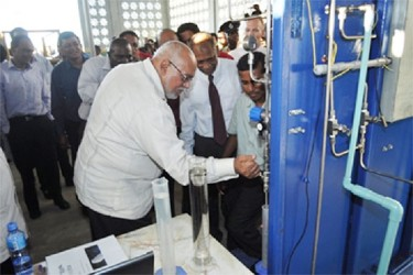 President Donald Ramotar drawing bio-fuel from the Albion plant at its launching (GINA photo)