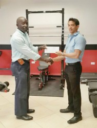 CEO of Fitness Express, Jamie McDonald, hands over the sponsorship cheque to Committee Member of the Guyana Amateur Powerlifting Federation (GAPF), Winston Stoby to aid in this year's novices and junior championships set April 5 at the National Gymnasium.