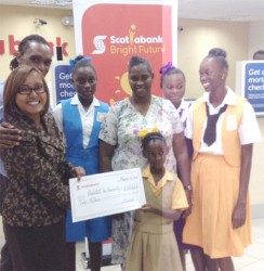Jennifer Cipriani of Scotiabank (far left) hands over a symbolic $2 million cheque to the youngest of Althea Boucher's four daughters as the proud mother, her other three daughters and a Habitat for Humanity representative look on.