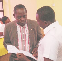 Vice-Chancellor Jacob Opadeyi (left) accepts the summons from the court marshal yesterday.