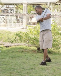 Ruplall Dudnauth taking a  swing at a golf ball in his yard.