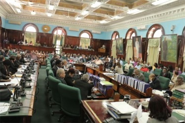 Parliamentarians kill time as they await the arrival of Finance Minister Dr Ashni Singh for the 2014 national budget presentation yesterday. (Photo by Arian Browne)
