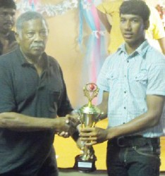 Basil Butcher hands over the Under-19 Cricketer of the Year trophy to Gudakesh Motie.