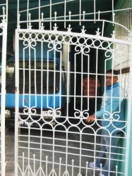 Khemraj Budhram standing behind the locked gate that trapped Aunty Baby and her attacker in the house.