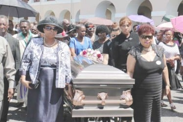 The casket with the remains of former APNU MP and Attorney at Law Deborah Backer being escorted yesterday afternoon  by APNU MPs Amna Ally (right) and Volda Lawrence from Public Buildings where a ceremony was held. (Arian Browne photo)