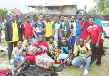The winning Bermine team with Coach Carl Moore (far left in the black jacket) and PMCC President Vickram Seubarran (far right I the red top) (Orlando Charles photo)