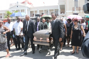 The coffin bearing the remains of former APNU MP and Attorney at law Deborah Backer being led from the Public Buildings yesterday to the St. Andrew's Kirk by APNU's Joe Harmon (left) and Basil Williams.