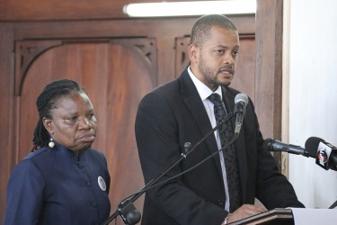 Head of the Guyana Bar Association Ronald Burch-Smith and Attorney at law Emily Dodson paying their last respects to Deborah Backer