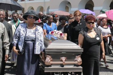 The casket with the remains of former APNU MP and Attorney at Law Deborah Backer being escorted this afternoon  by APNU MPs Amna Ally (right) and Volda Lawrence from Public Buildings where a ceremony was held to the St Andrew's Kirk.
