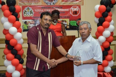Lloyd Henrietto (right) receiving the award yesterday at the Pegasus Hotel for the most Outstanding Volunteer from Manager, National Tuberculosis Programme, Dr. Jeetendra Mohanlall (GINA photo)