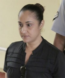 Murder accused Carolan Lynch being escorted by a policewoman to the holding cell at the Georgetown Magistrates' Courts after the first session of her PI.