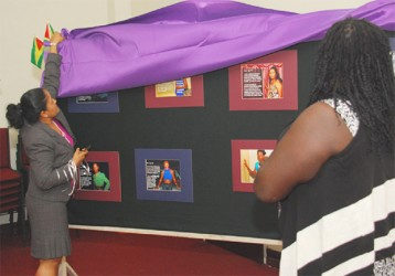 Dr. Shanti Singh (left)  unveils the exhibition as Quincy McEwan, Director of Guyana Trans United looks on. (SASOD photo)